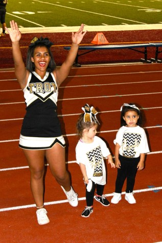 Alyanna Myrick, junior, stands with children in a cheer clinic Topeka High's cheer and dance team had throughout the week.