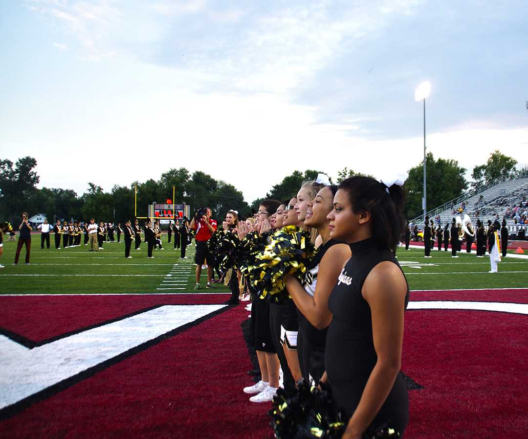 The Topeka High School cheer and dance teams stand at the ready before Topeka High's Football team bursts onto the field for their pregame entrance.