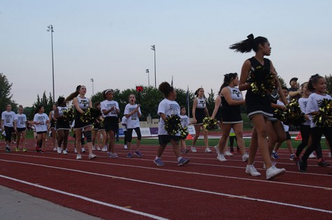 The Cheerleaders and kids walk the track during pre game.