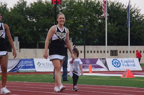 Kiera Beatty, junior cheerleader, walks with a kid around the track