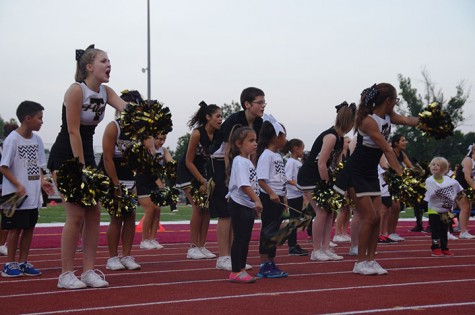 The Cheerleaders cheer with the kids on the sidelines