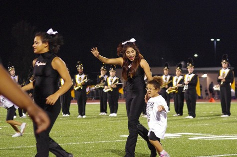 Shalma Reyes, Senior dancer, dances with a kid off the field after the half time performance