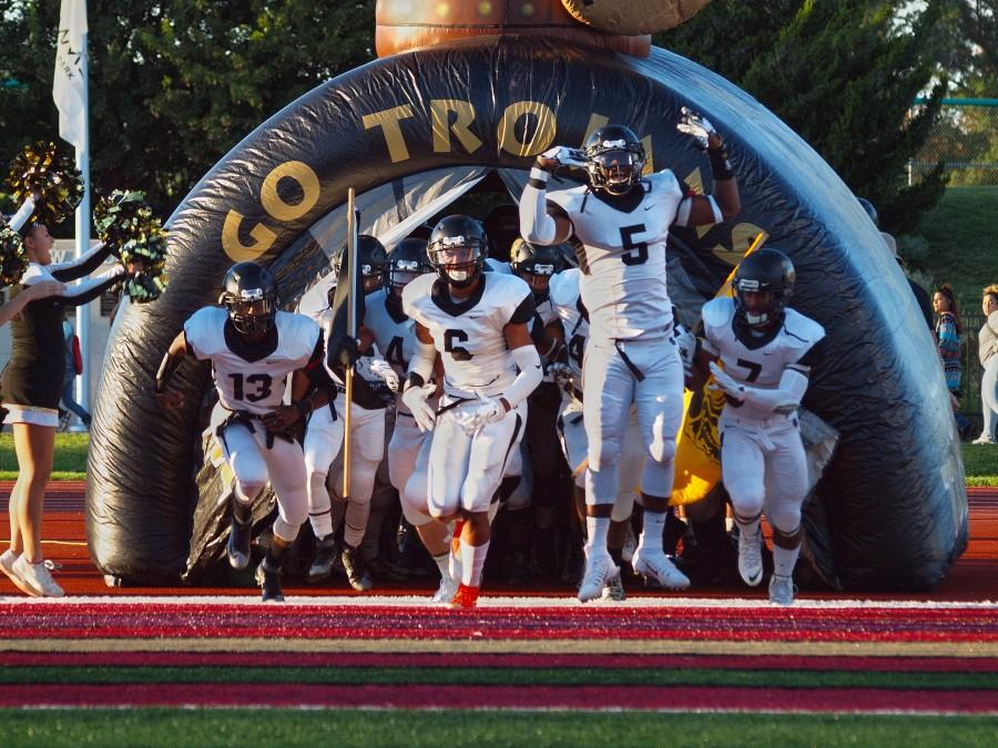 The Trojans, led by seniors Mike McCoy (5) and Dante Brooks (6), burst onto the field before their game against Topeka West High School.