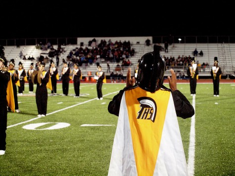 Drum major Kalese Warfield, junior, looks on to the field as she conducts the Trojan Marching Band.