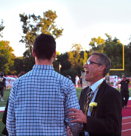 Associate Principal Robert Hays chats it up on the sidelines with 2014 Homecoming King Joel Long.