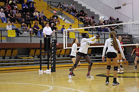 Erica Burch (15), junior, hits the ball with the support of her teammates Maliyah Malone (3), freshman, to the right of her and Jolie Regnier (4), sophomore, to the left.