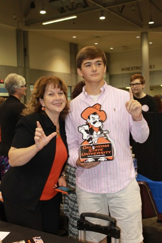 """Tristan Weichert, junior, and an OSU (Oklahoma State University)  administrator are """"guns up"""" for the Cow Pokes at the Kansas & Career Fair at the Kansas Expocenter."""
