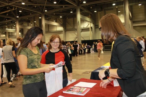 Ale Villegas and Francesca Kelly, seniors, take in a booth at the College & Career Fair at the Kansas Expocenter.