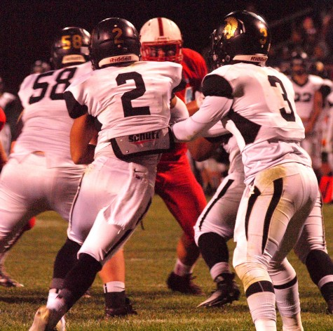 Quarterback Corey Thomas (3) reads a defensive end to make a handoff to running back Saylor Caraway (2), senior.
