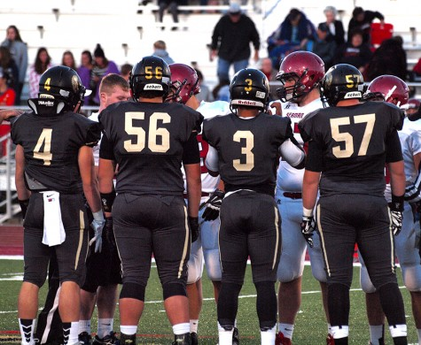 Trojan captains for the game- Jacob Anderson (4), senior, Ryan Luna (56), senior, Corey Thomas (3), junior, and William Wagemaker (57), junior- out at the 50 yard line for the pre-game coin toss.