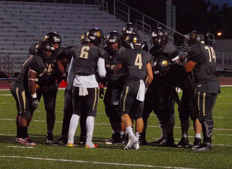 Topeka High's offensive power package huddles near the goal line before punching in a score by senior Dante Brooks at the end of the first half.