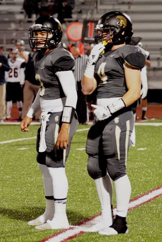 Quarterback Corey Thomas, junior, and Jacob Anderson, senior, look to the sideline for an audible called by the coaching staff in the first quarter of the senior night game against Manhattan.