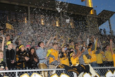 "The Topeka High student section, which was decked out in gold for their ""Gold Out"" theme, throws newspaper confetti in the air at the start of the senior night game."