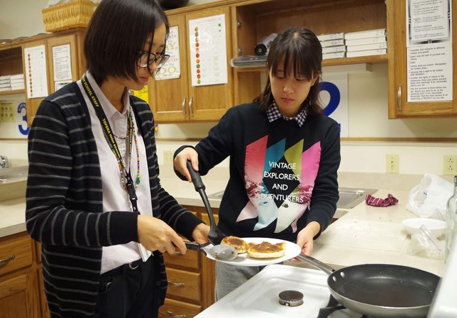 Vogel assisting an exchange student from Washburn make her pancake.
