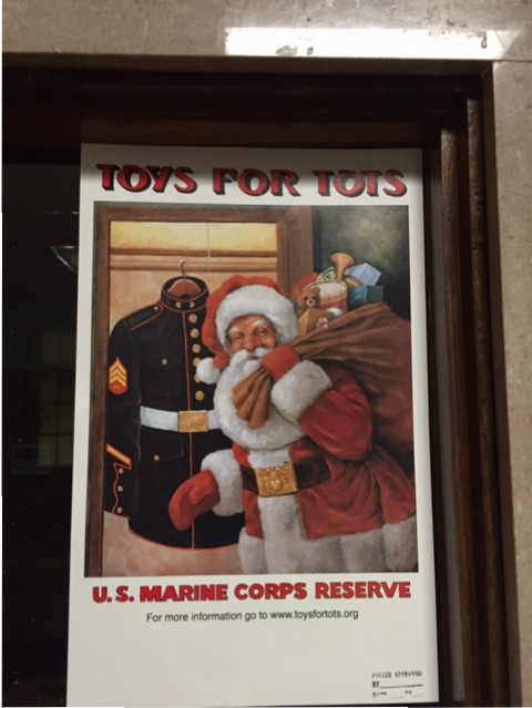 A poster for Toys for Tots hanging in the main hallway by the office.