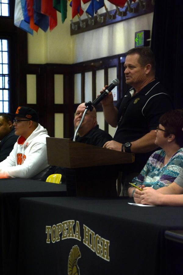 Head Coach Walt Alexander speaks at the podium of Topeka High Footballs National Signing Day event.