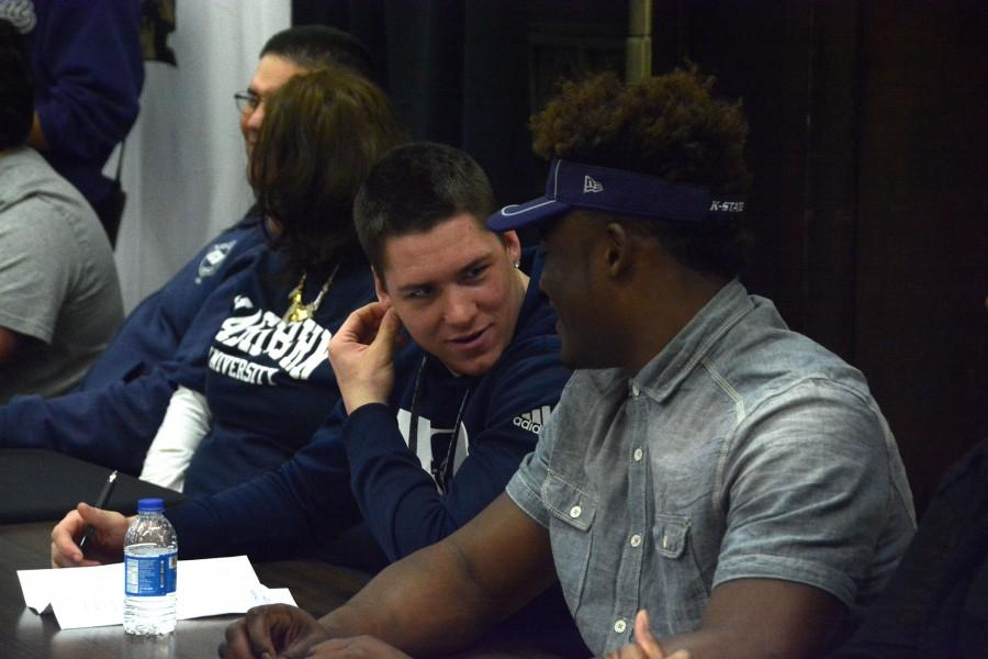 Jacob Anderson and Mike McCoy, seniors, share a word before Topeka High Schools National Signing Day event. Anderson, who played linebacker for the Trojans, signed his letter of intent to play at Washburn University. Washburns program currently has four former Trojans, Jake Regnier (c/o 2015), Austin Tillman (c/o 2014), Raymond Solis (c/o 2013), and Jared Butler (c/o 2013).