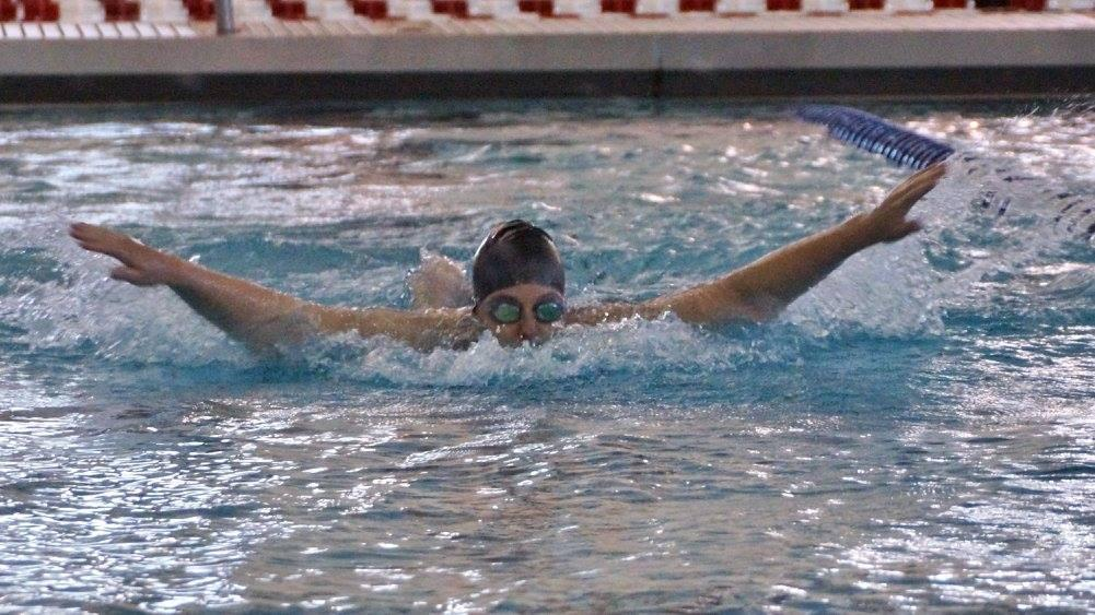 Keira Beatty, junior, swims butterfly at a meet. Photo by Craig Strever.