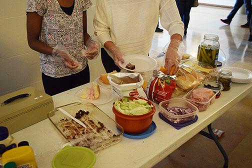 Nate Karsky, junior, Maya McFadden, junior, and TKuyhh Williamson, junior, making sandwiches for Market day.