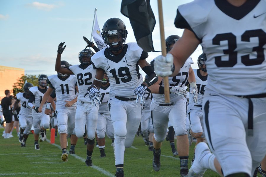 Joel Matlock (19), senior, smiles for the camera as he runs for the sideline before Friday Nights Topeka High-Hayden football game. Matlock was a part of a defense which allowed only 6 second half points against the Hayden Wildcats