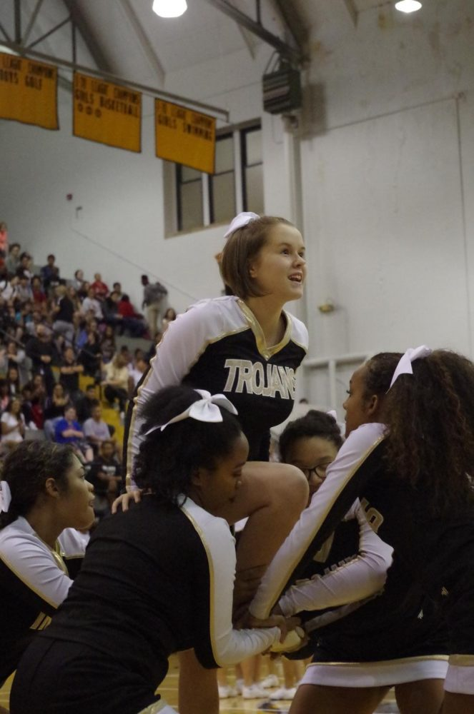 Madison Jacques, sophomore, prepares to be thrown in the air for her stunt.