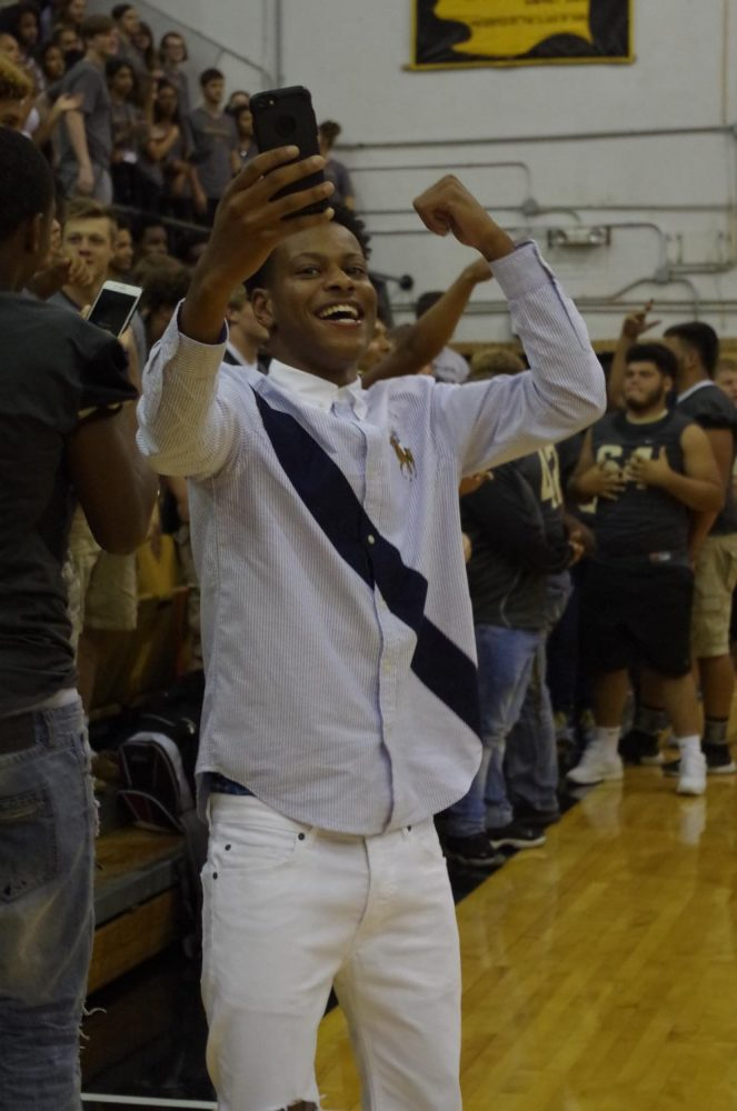Marvelle Yates, senior, takes a snapchat video of the crowd.