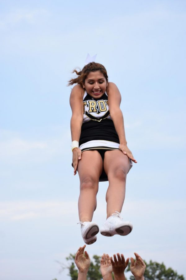 Roshele Reyes-Bolanos, junior, flies while performing a stunt.