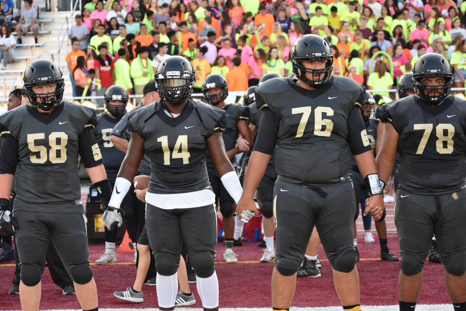 Seniors Tanner Matthias, Xavier Dunbar, Matthew Garza, and Tucker Richey hold hands in preparation to walk out on the field. (File Photo)