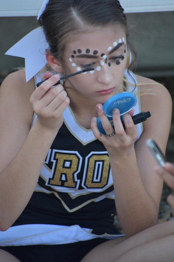 Alaina Miller, sophomore, applies makeup before a football game.