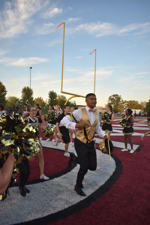 Darren Canty runs out onto the field behind the football players after being crowned homecoming king.