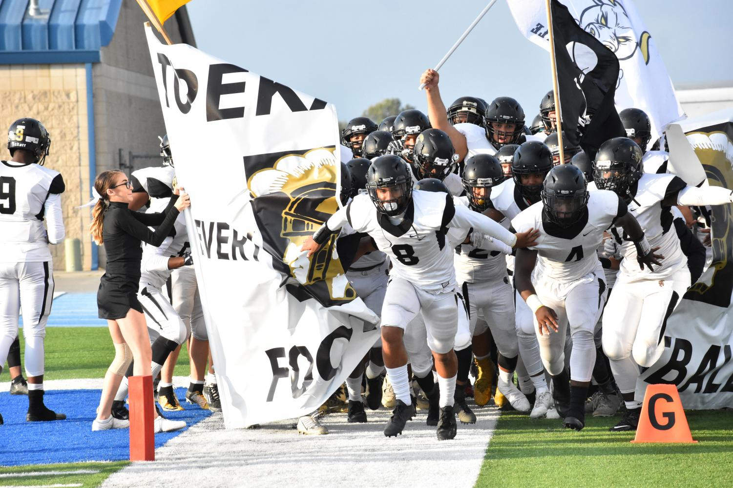 The+football+team+runs+out+onto+the+field+before+their+game+against+Washburn+Rural.+