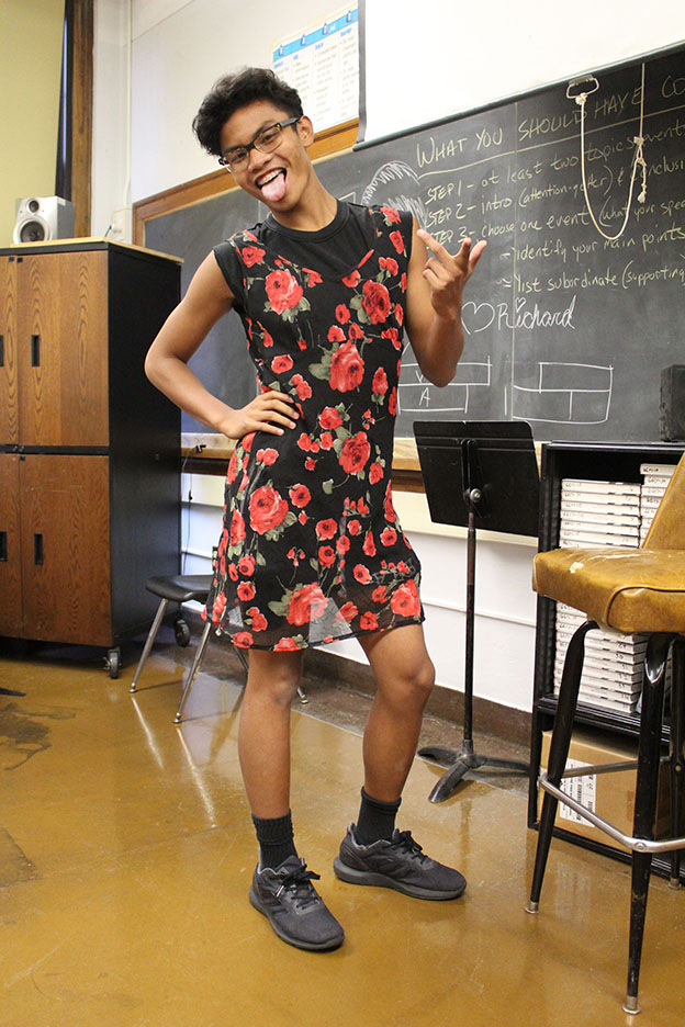 Gabriel Obenieta, sophomore, poses in his black dress with roses.