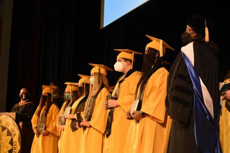 Marleny Galvan Retana, Sephra Caballero, Tessaira Evans, Marisabel Munoz, Andrew Anderson, and Kenade Wilkerson posing for a picture after becoming official graduates of Topeka High School.