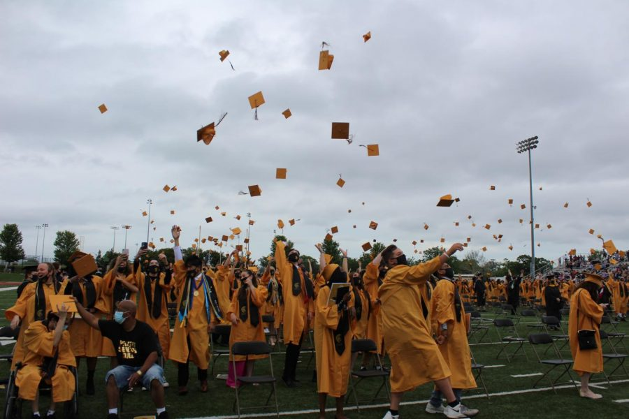 A group of graduates throwing their caps as the commencement ceremony ends.