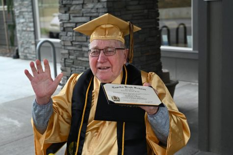 Clarence Frost holding his Topeka High School diploma after waiting 75 years